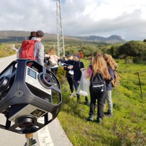 Close up of camera rig with blurred group of students by a roadside in the background