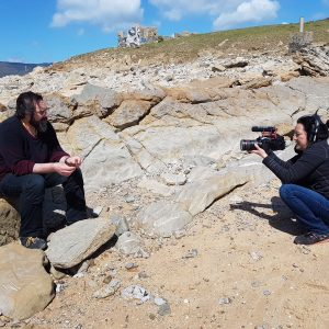A man sitting on a rock whilst a woman points a camera at him.