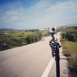 A camera on a tripod on another tripod by a roadside.